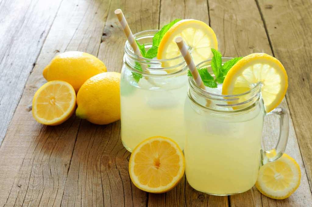 Two glasses of lemonade with lemons.